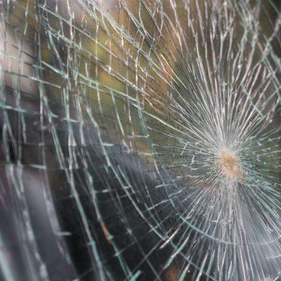 Glass broken cracks splinters in front of car ( Filtered image processed vintage effect. )